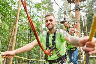 Mann und sein Team beim Klettern im Hochseilgarten