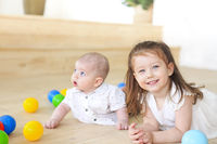 Baby boy and his sister playing with balls. Colorful toys for kids. Kids in play room