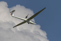 Motorized glider in a blue cloudy sky