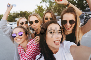 Six young beautiful girls looking at the camera and taking a selfie