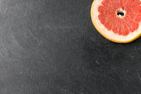 close up of fresh juicy grapefruit on slate board