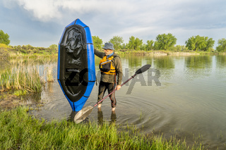 senior male with a packraft