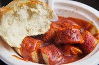 Scharfe Currywurst mit Brötchen