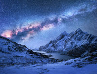 Bright Milky Way over snow covered mountains and sea bay at night