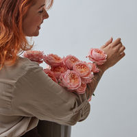 Sexy red-haired girl with a tattoo, holding a beautiful bouquet of pink roses in a vase around a gray background with copy space. Postcard to Valentine's day