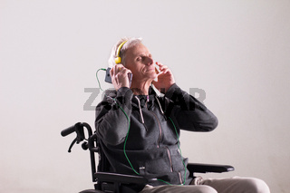 Disabled man listening to music in wheechair.