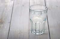 Glass of water on white wooden table