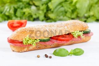 Sandwich Baguette Vollkorn Brötchen belegt mit Salami Schinken auf Holzbrett