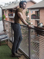 Handsome dark haired young man standing in a balcony