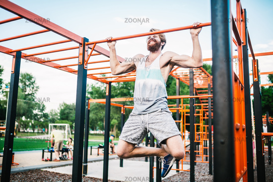 strong athlete doing pull-up on horizontal bar. Muscular man doing pull ups on horizontal bar in park. Gymnastic Bar During Workout. training strongmanoutdoor park gym. Man Doing Exercise gym Outdoor