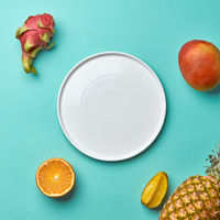 Different tropical fruits and empty white plate on a blue background with copy space. Flat lay