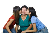 Daughters kissing mother