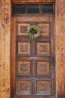 old shabby wooden front door with wreath