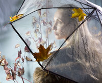 woman under a transparent umbrella with autumn leaves