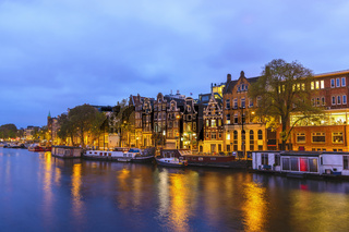 Amsterdam Netherlands, night city skyline at canal waterfront