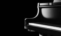 closeup black grand piano isolated on black background