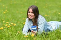 Woman laying on grass with coffee