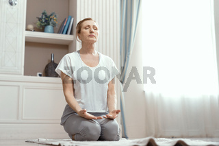 Attractive mature woman is practicing yoga in peace
