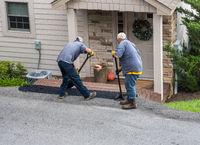 Workers applying extra blacktop onto asphalt street