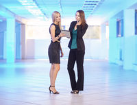 Two girls in the office with tablet and phone in hand. Young women discuss office work