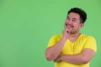 Happy young handsome overweight Asian man thinking