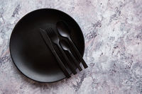Top view of black empty plate on marble stone background