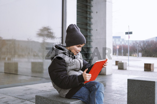 7 year old boy playing online game on tablet computer outdoors in winter