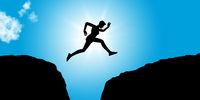 Fitness Person springt voller Mut zwischen Felsen