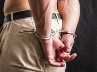 Back of shirtless man with handcuffs