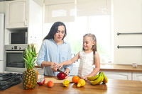 Little girl with her mother in the kitchen preparing a fresh fruit salad