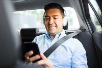 passenger with headphones using smartphone in car