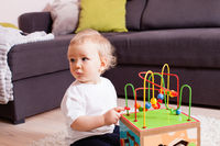 Infant baby boy playing indoors with toy sitting on soft carpet