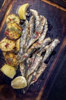 Traditional Spanish barbecue sardine with fries as top view on a cutting board