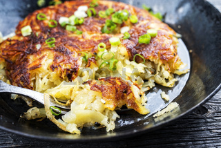 Traditional Swiss hash browns as side dish with leek as closeup in a frying pan