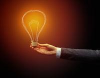Hand holding light bulb on dark background