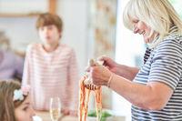 Großmutter serviert Enkel Kindern Spaghetti