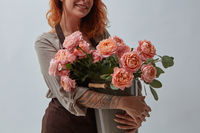 Young red-haired girl with a tattoo holding a bouquet of pink roses around a gray background with copy space. Happy Mother's Day