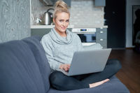 Middle aged woman sitting on sofa in her living room and working on laptop