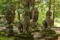 Four lion and snake statues in trees