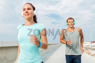 couple with headphones running outdoors