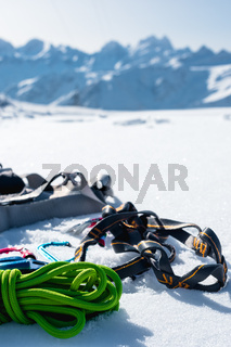 Winter set of equipment of an ice climber with carabiner wounds and a camp thermos against the background of snow-capped mountains . Copy space for the designer