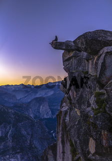 Man sits on the edge of a cliff at Glacier Point