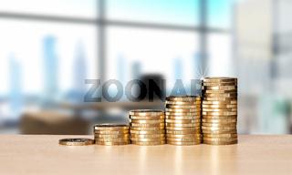 Stapel mit Münzen und Büro im Hintergrund