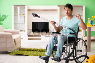 Disabled man on wheelchair vacuum cleaning house