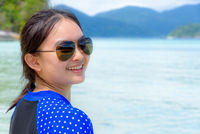 Face of a woman is smiling at the camera on the sea background