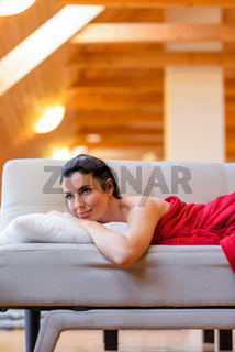A beautiful nude woman wrapped in a cozy blanket relaxing on the sofa