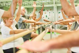 Gruppe Senioren trainiert Koordination an Ballettstange