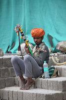 KANGRA DISTRICT, HIMACHAL PRADESH, INDIA, May 2017, Man on the streets playing music on musical intrument at McLeod Ganj