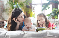 Mother reading a book with her daughter and son in bedroom