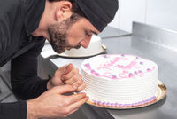 Handsome professional confectioner making a delicious cake in the pastry shop.